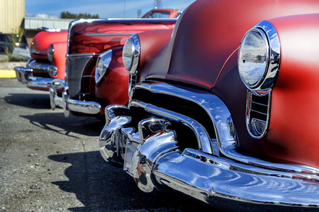 Three heavy front end red vintage cars lined up in a row.