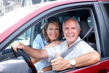 Married seniors sitting in a brand new car